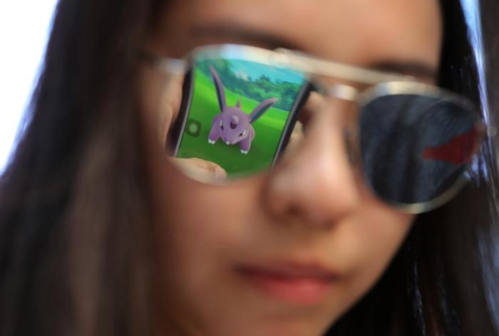 a-mobile-screen-is-reflected-on-a-fans-sunglasses-as-she-plays-pokemon-go-in-hong-kong-july-25-kin-cheungassociated-press